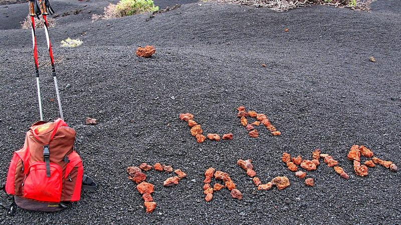 """Foto: Wanderrucksack und Schrift """"La Palma"""" mit Steinen gelegt, Lavasand"""